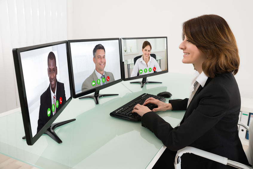 Business woman looking at monitors in virtual meeting